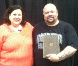 Dr. Lori standing next to man holding Freemasons book