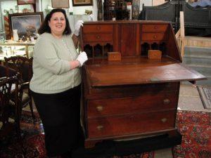 Dr. Lori standing next to antique desk