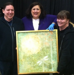 Dr. Lori standing with couple holding Robert Han Nong painting